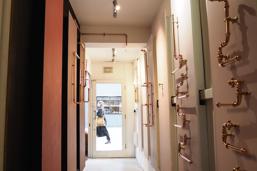 a woman walks by the entrance to the forster inc redchurch street office in shoreditch, where the new forster inc entryway design project is showcased, in collaboration with dogs body design and little greene paint co.