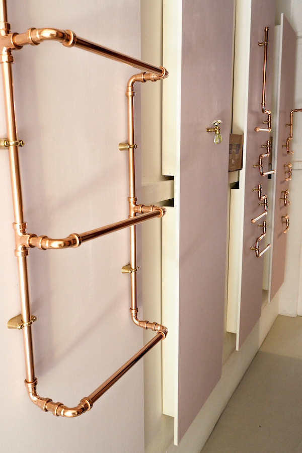 panels of pink from little greene paint co line the corridor of the forster inc hallway, showcasing dog's body copper pipework in various utilitarian purposes.