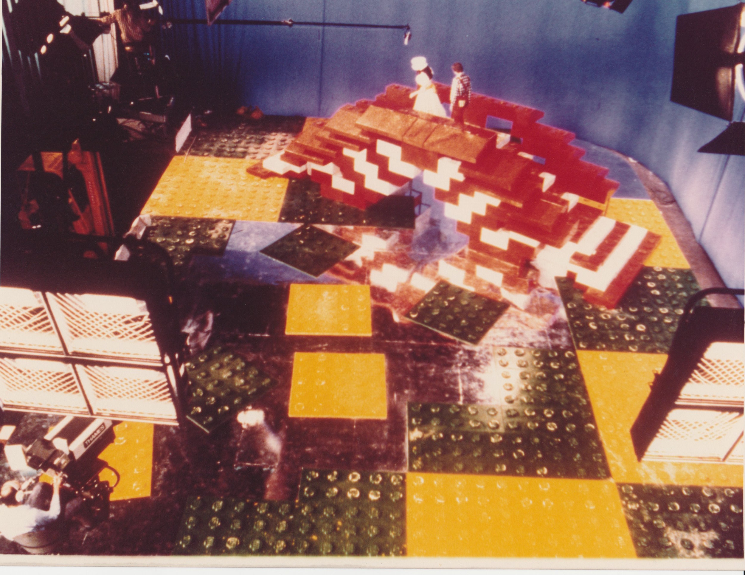 It got even worse…. - `Quincy`s Quest` was a live show, going out on Christmas day 1979 and so all props had to be on set in a working condition - definitely no second chance.The even larger mouldings for the Lego flooring had proved to be a bit of a challenge to make.Although Andrew had the facility of the overhead gantry in the workshop, which had previously been used for lifting giant marine diesel engines which were used for generating electricity for the studios, the weight and size of these moulds proved difficult to clamp tight.The internal pressure generated in the moulds was about 400 tons and so the slightest leak in a seal would result in hot molten plastic ejecting like Vesuvius and thus coating the ceiling of the workshop with a skin of insulation and of course any unfortunate workers in the near vicinity.A quick change of tactics caused Andrew to abandon the moulding process and quickly make thousands of individual round Lego locking pieces to glue onto wooden boards. They would then have to be painted in yellow & green to match real Lego.It was the day before Christmas and the deadline was near and so Andrew mustered everyone he could convince to help, even calling on his old friend Trevor Baylis, (clockwork radio inventor) to come out and work a 24 hour shift on Christmas eve.Andrew`s idea was to paint the giant lego floor with Polyester fibreglass resin. It should cure quickly to a hard resilient surface and could be pigmented to any colour.On a cold winter's night, this did not happen - it would not cure and remained a sticky mess even when presented on set.Complaints from the actors were rife as their shoes parted from their feet, especially noticeable in the dance sequences.Andrew did not attend the shoot that day and waited for the Christmas holidays for it all to blow over…..or at least let the paint dry, In the hope that the show was a spectacular success and everyone would forget the cock- ups.