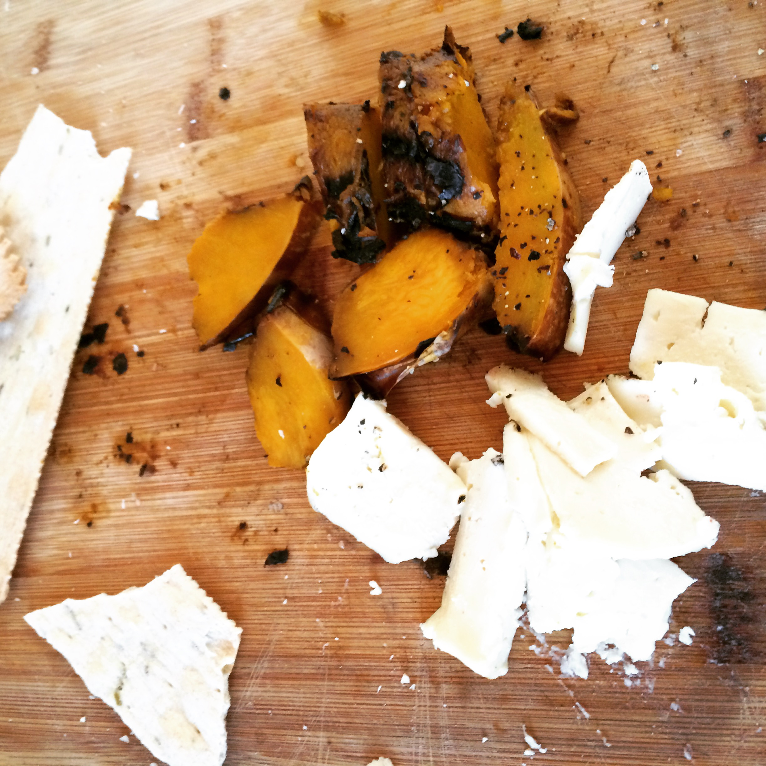 Leftover grilled butternut squash, queso blanco, and Trader Joe's crackers, served as an impromptu appetizer at our home.