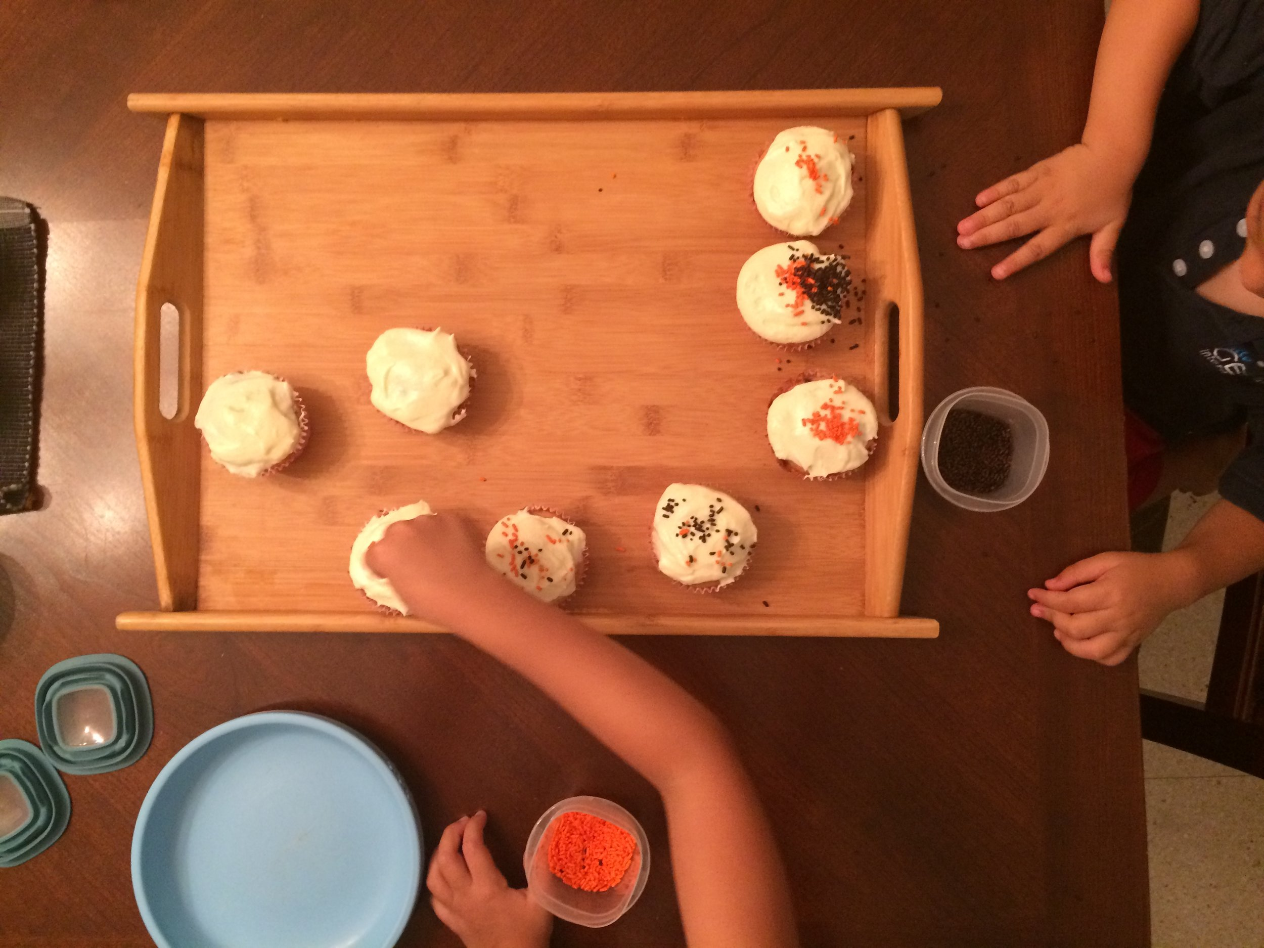 My kids decorating chocolate chip muffins with cream cheese frosting.