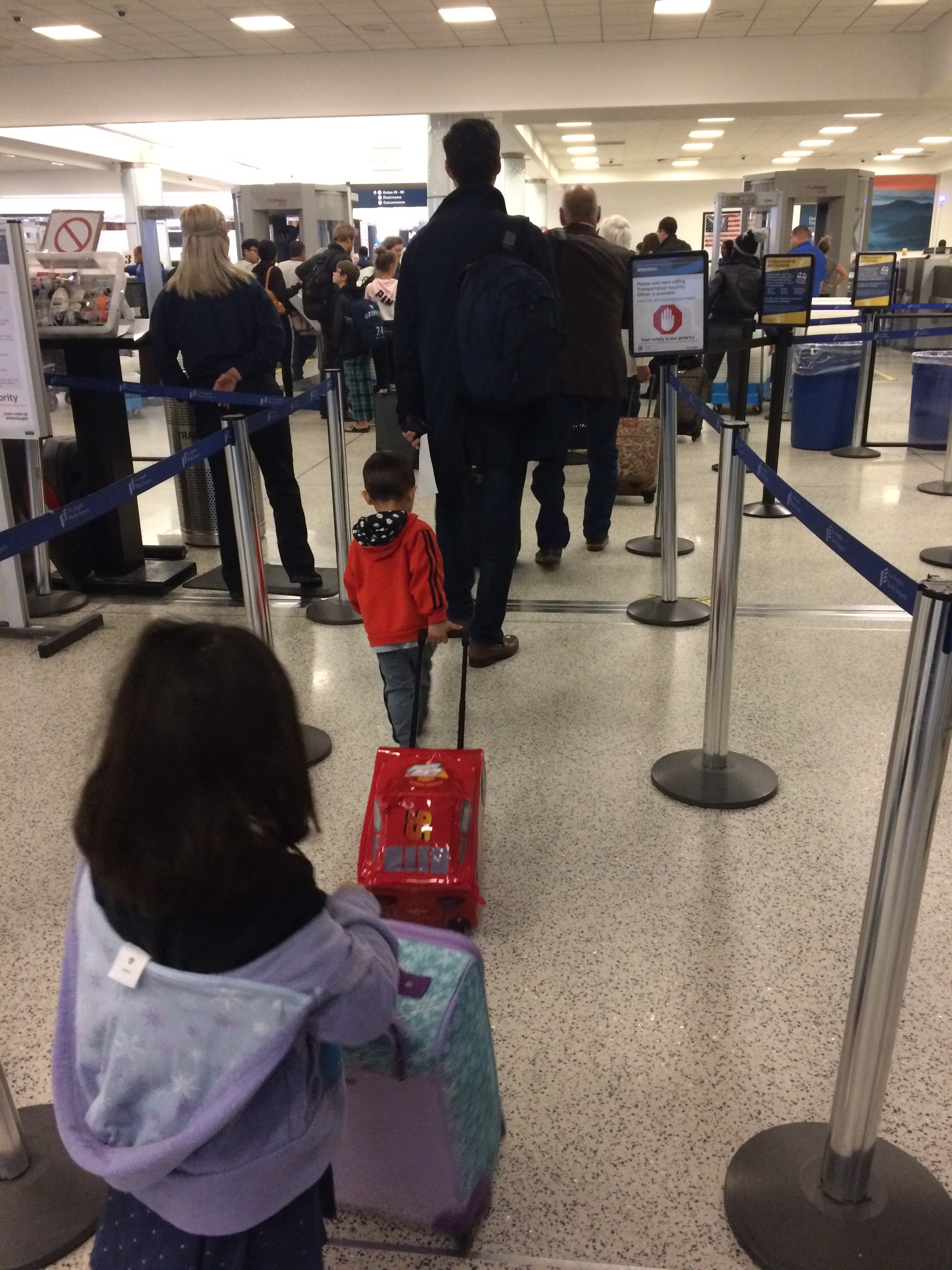 My two little travel warriors, heading through security before we were stopped and forced to dump out all the contents of the my kids' roller board bags.