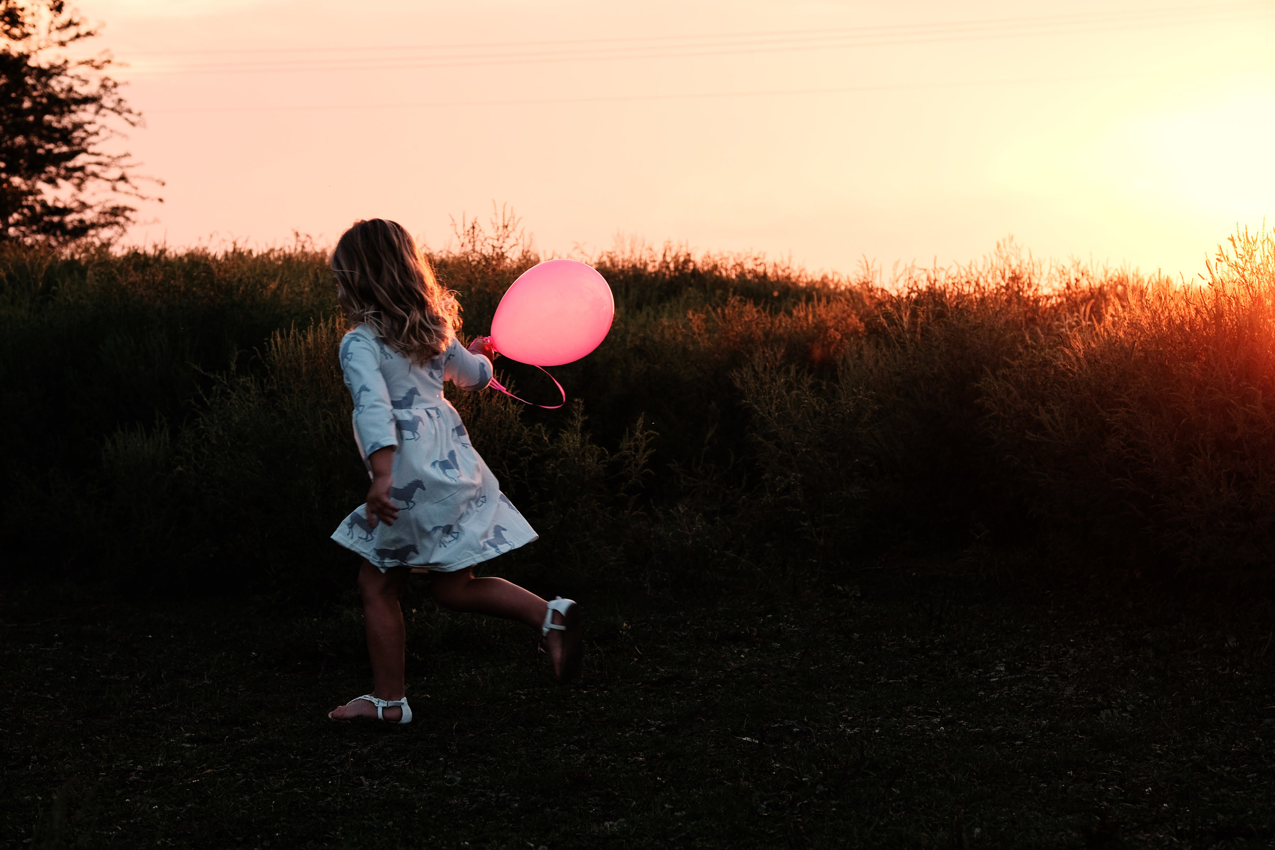A girl running with a balloon in the sunset.