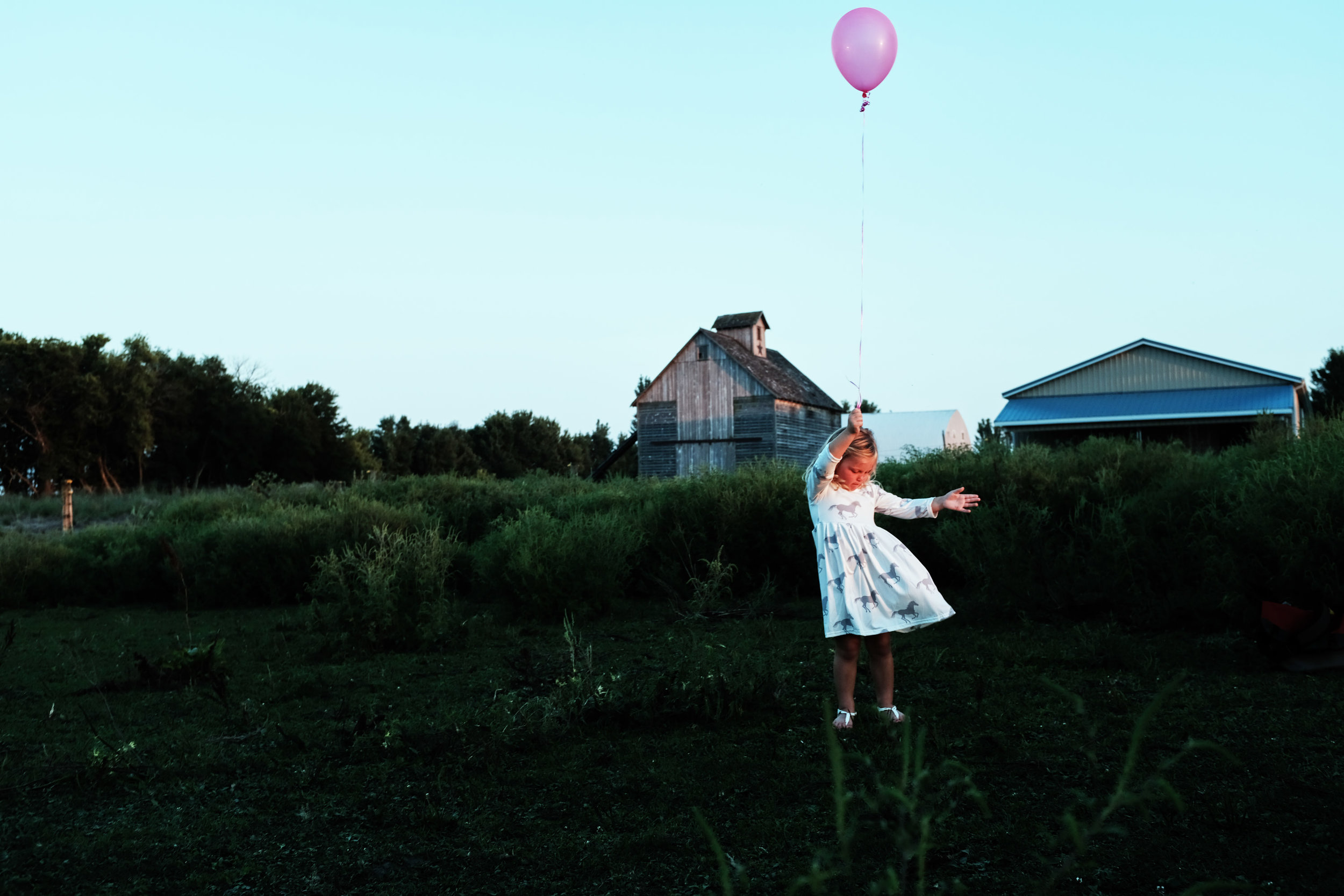 A girl playing with a balloon in a field near Ames, Iowa.
