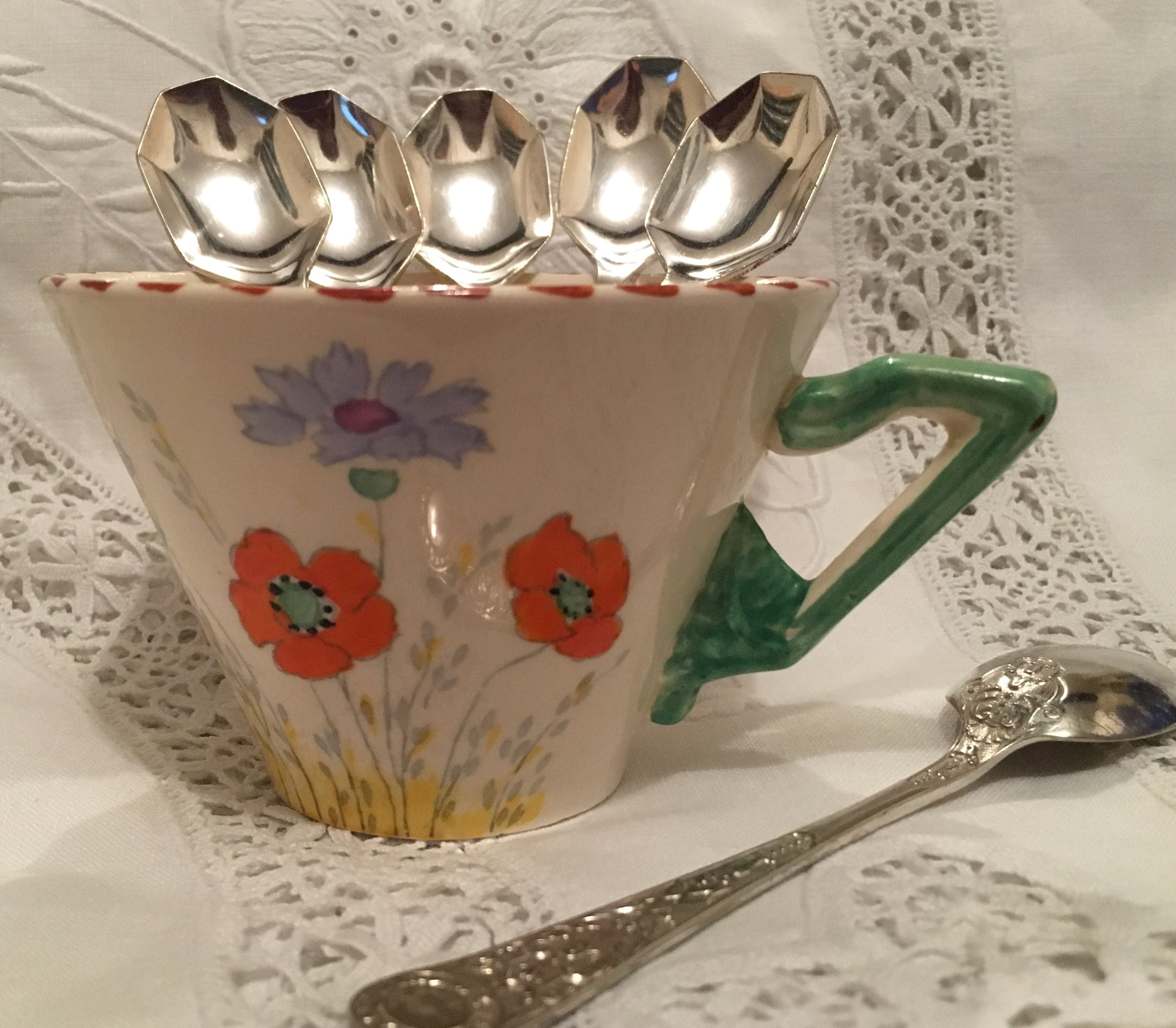 Six beautiful, vintage teaspoons in antique tea cup.