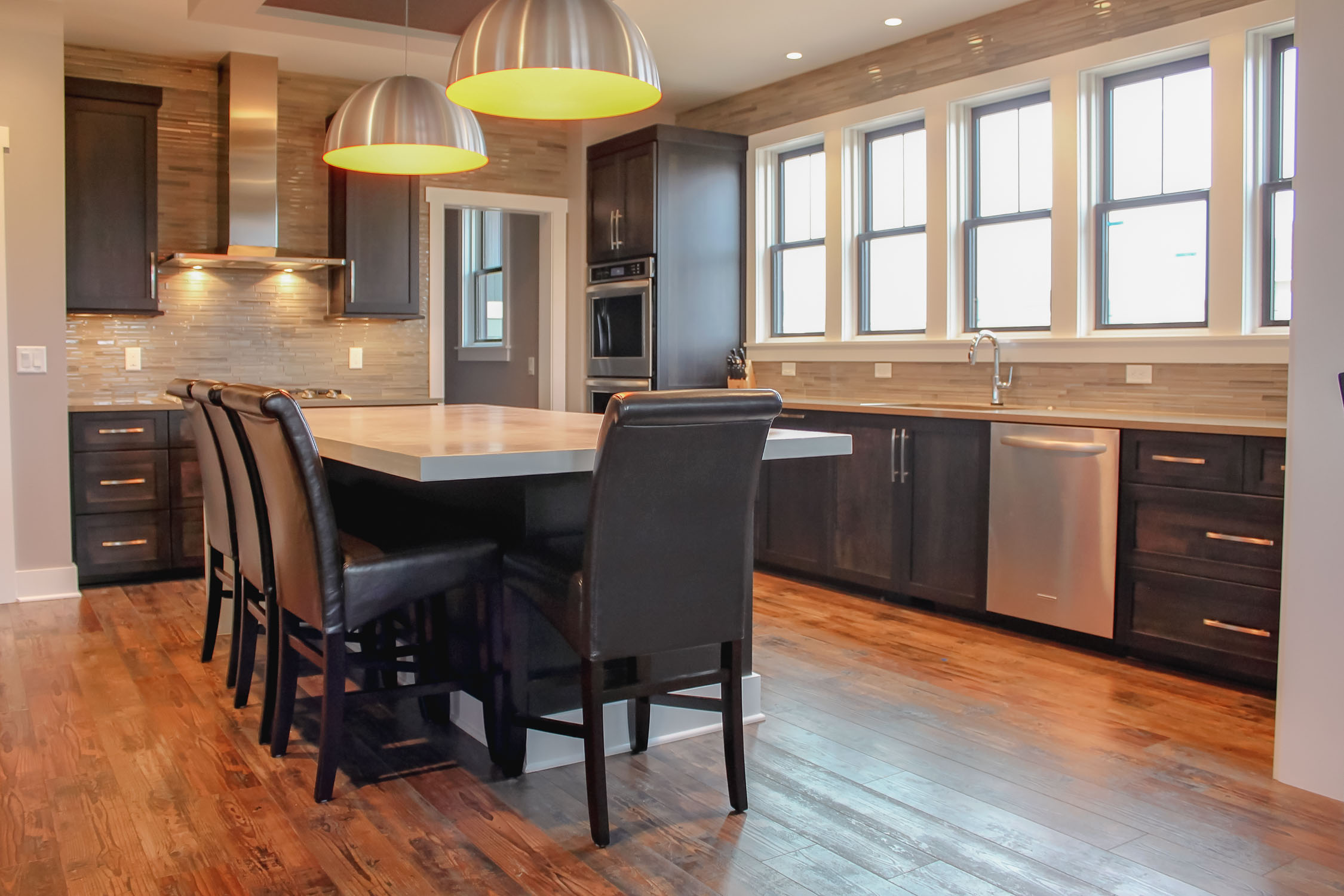 A modern kitchen design with brushed stainless steel pendants