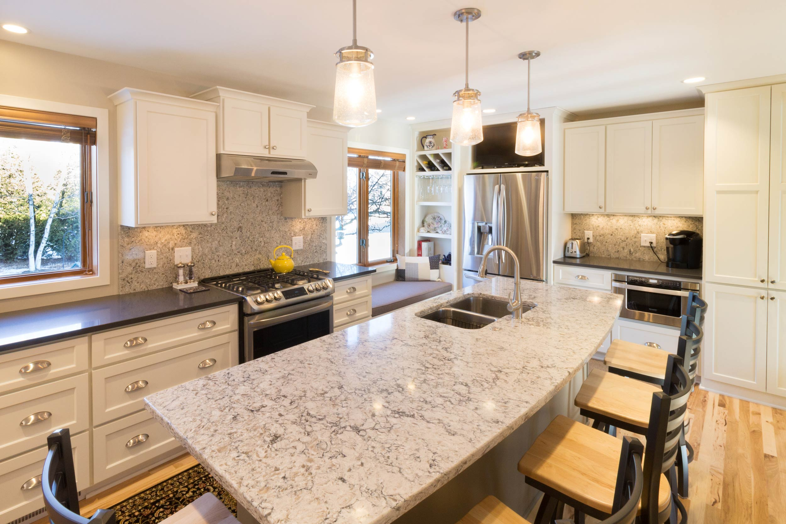 - Quartz countertop used as backsplash, matching the island top.