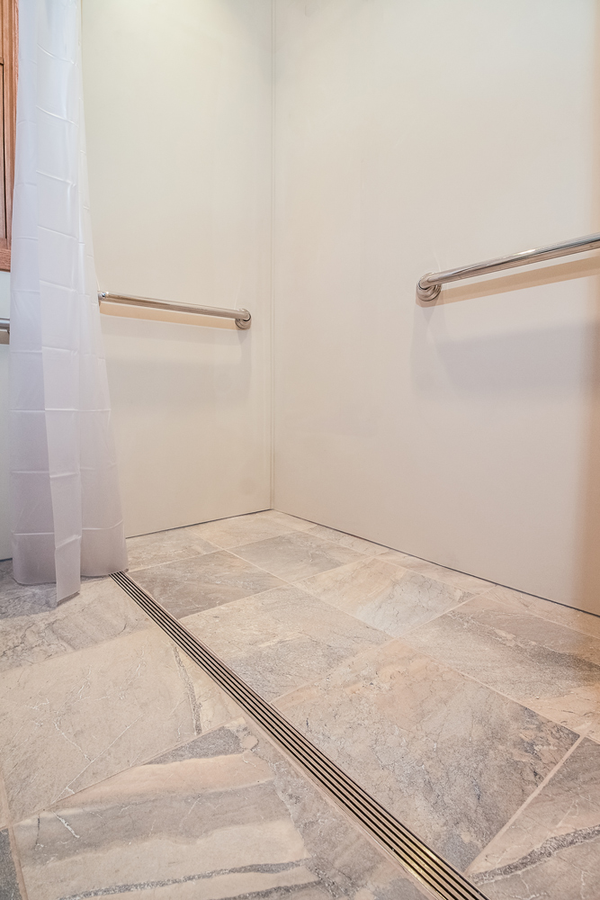 - A linear drain and fully-waterproofed bathroom floor allow this former bathtub to become a barrier-free shower.