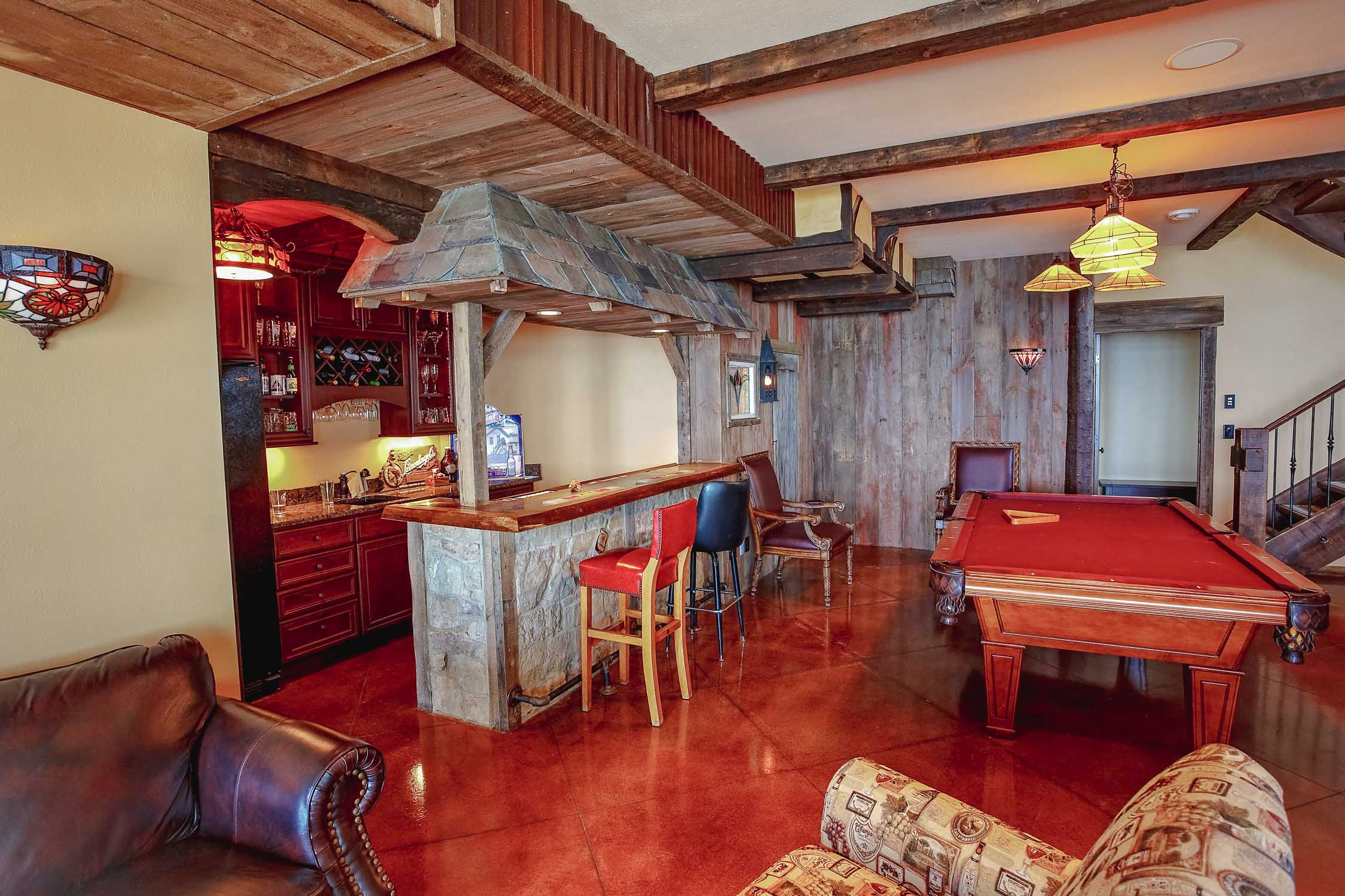the basement floor of this one-of-a-kind storybook lake house basement uses stained, acid-washed concrete for the finished flooring of the room.