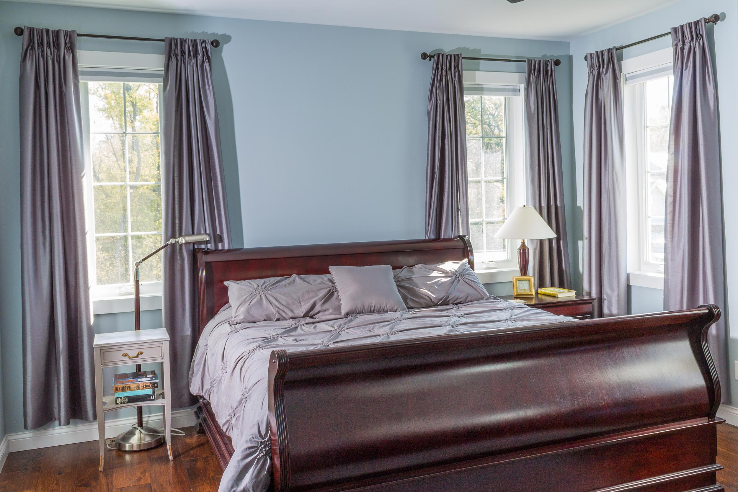 Master Bedroom Design with Sleigh Bed and View of Yard Beyond