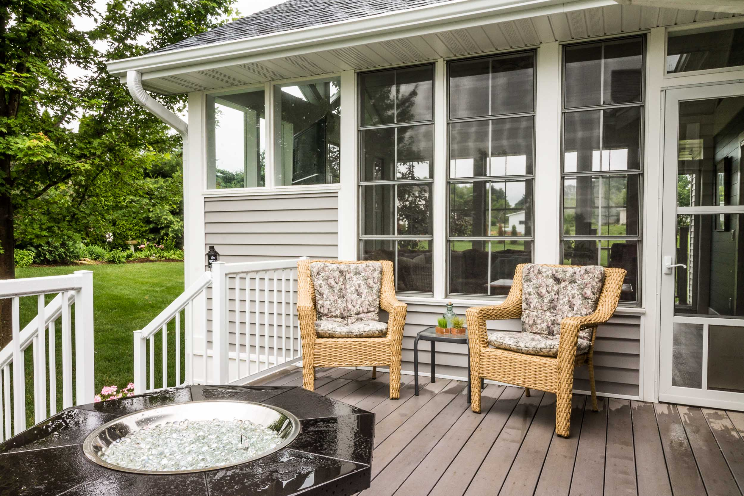 The deck is Secluded From The Neighbors By The Three Season Porch For Privacy