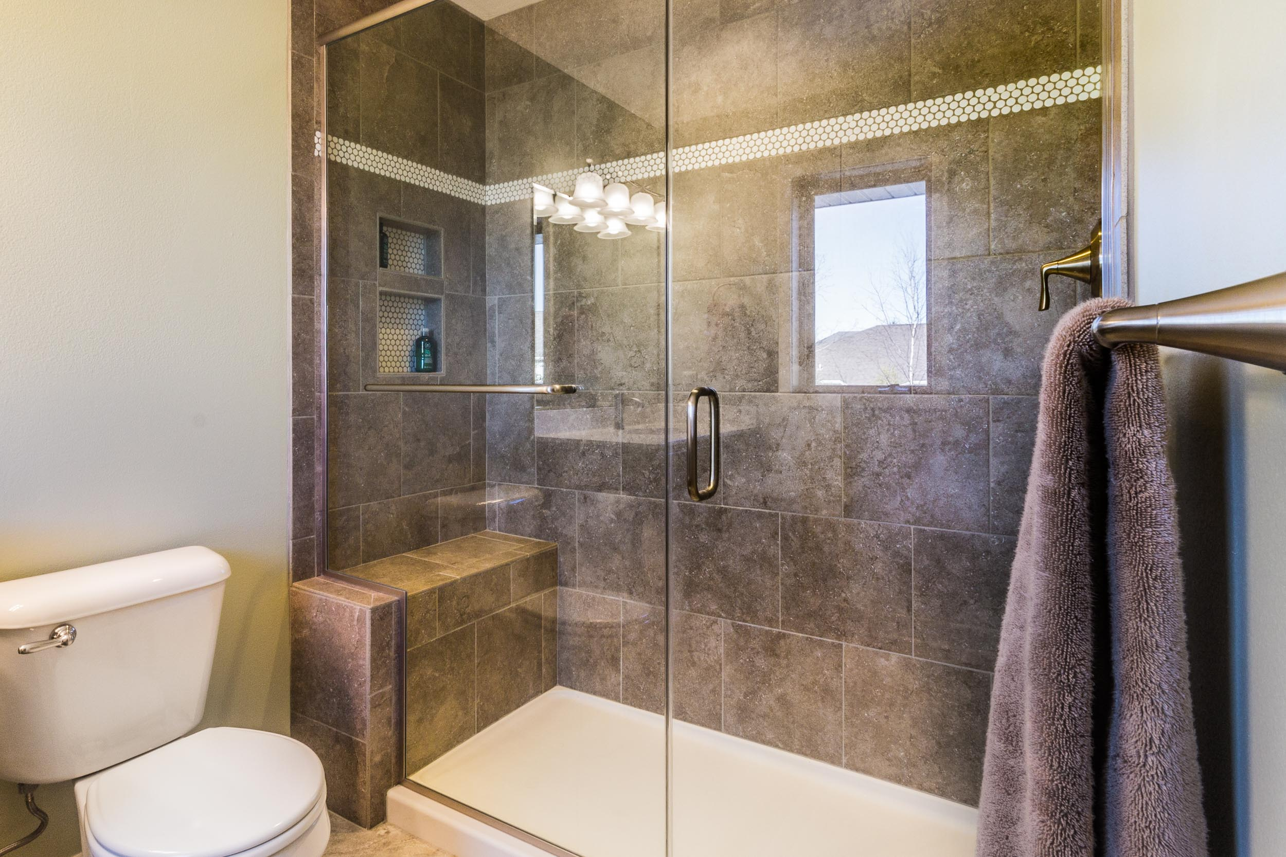 - The white penny tile stripe complements the white shower base, and the penny shape is evident because the dark grout used contrasts with it.