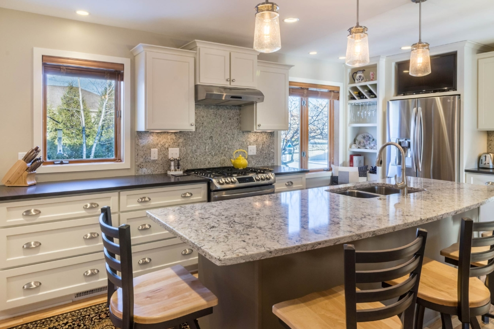 Quartz as Backsplash - The same Quartz countertop that was used on the island is repeated as a backsplash behind the slide-in range and under the adjacent cabinets at this kitchen remodel in Waunakee, WI.