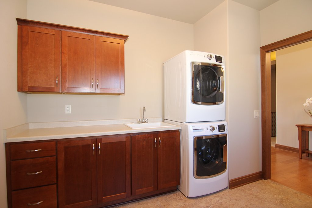 Stacked Washer & Dryer Laundry Room Design - A laundry room with a stacked washer & dryer allows more room for countertop and cabinet storage.