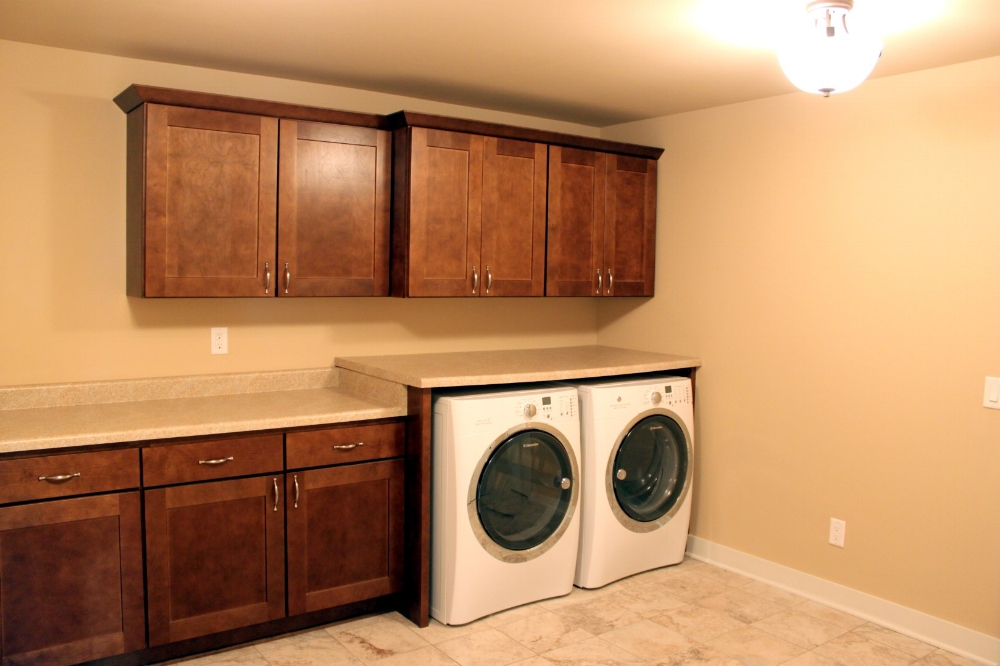 Tall Laundry Machines with Countertop - It can take a little more work but countertops can extend over a taller washer & dryer. In this case, and end panel was used to support the raised countertop.