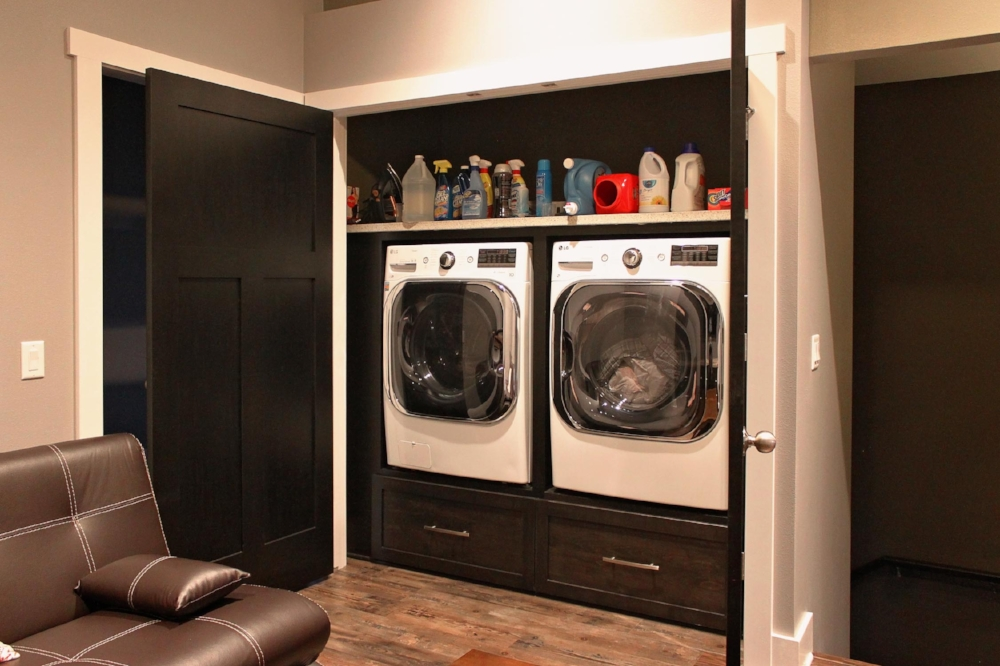 Laundry Closet Design - This laundry closet uses full-size machines. Cabinet drawers were built to create a riser that perfectly matches the woodwork in the rest of the home. A shelf above provides space for linen storage and cleaning supplies.