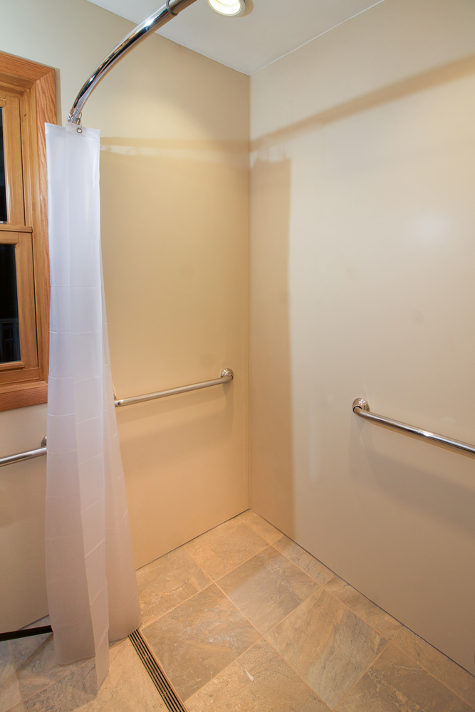 ADA Accessible Shower - This doorless shower is fully ADA accessible and was retrofit into the space of a standard bathtub. A linear drain was installed on the floor, and the whole bathroom floor is waterproofed to prevent damage from any incidental overspray that makes it past the shower drain.