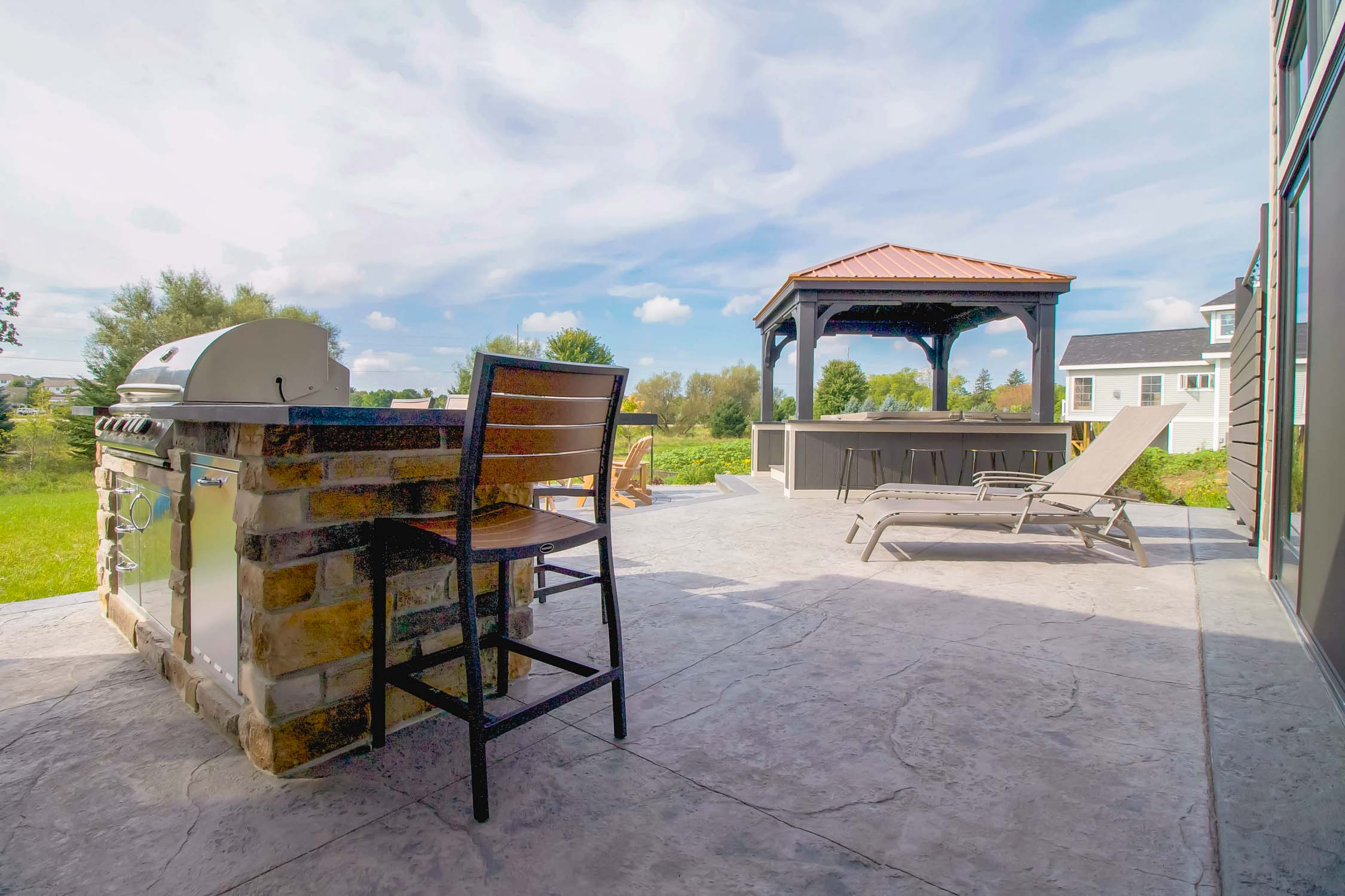 - This patio includes options for lounging in a chaise, seating at the grilling station, a bar by the hot tub, and Adirondack chairs by the fire pit.