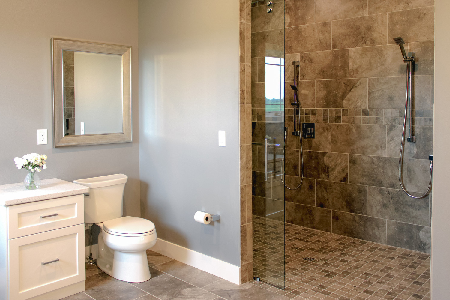 A roll-in shower with a barn-style shower door - This ADA-accessible bathroom incorporates universal design for the differing abilities of both the husband and wife. A barn door is used for the shower door of the zero-entry shower.