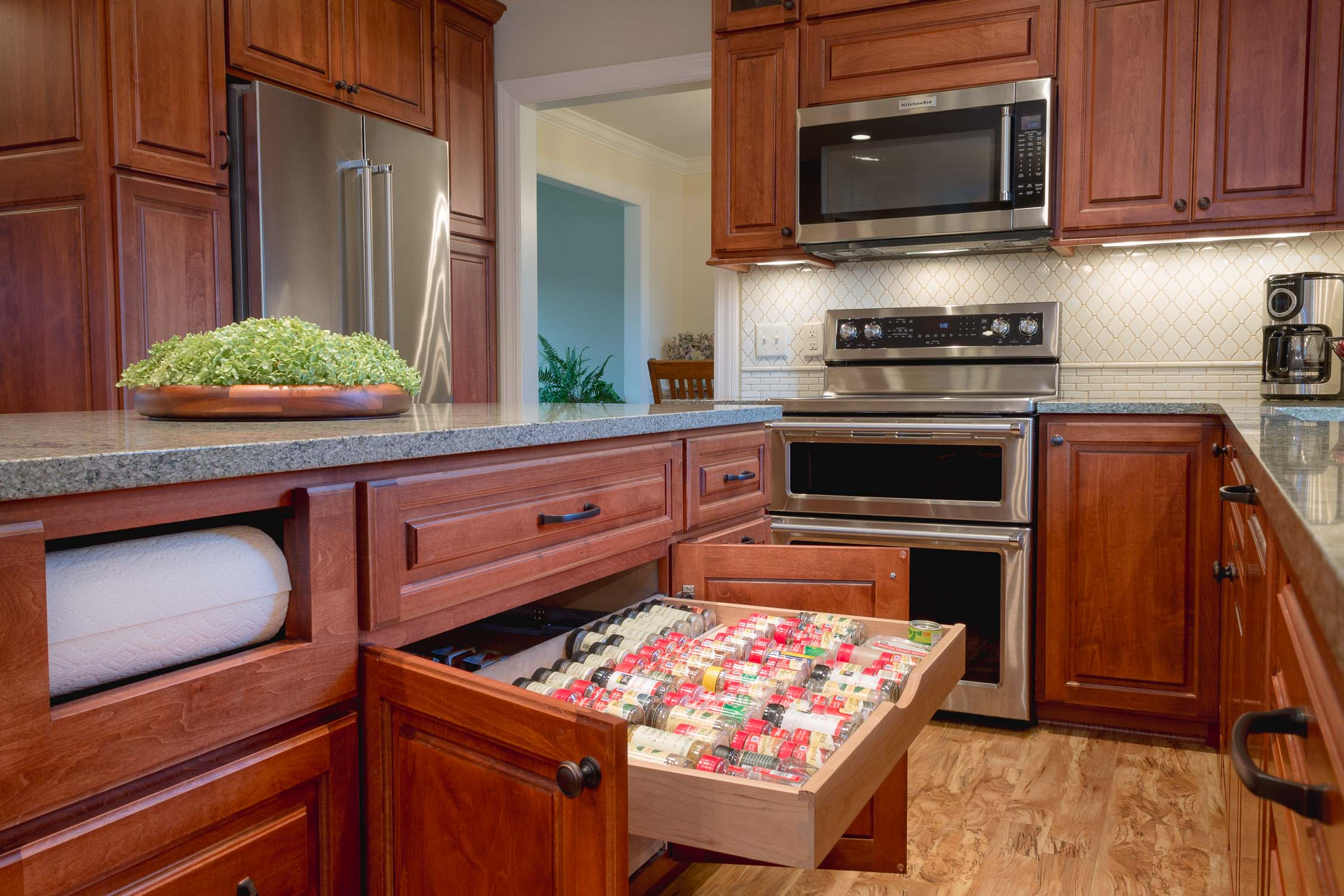 - This kitchen provides creative storage solutions including decorative transom cabinets (barely visible top left of microwave) and built-in spice drawer and paper towel holders. Click any photo to see more on these projects.
