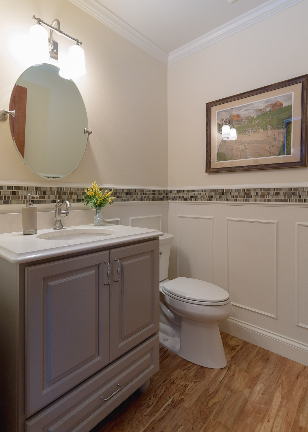 - This powder room integrates a furniture-style vanity cabinet with bun feet, wainscot, and a tile strip.