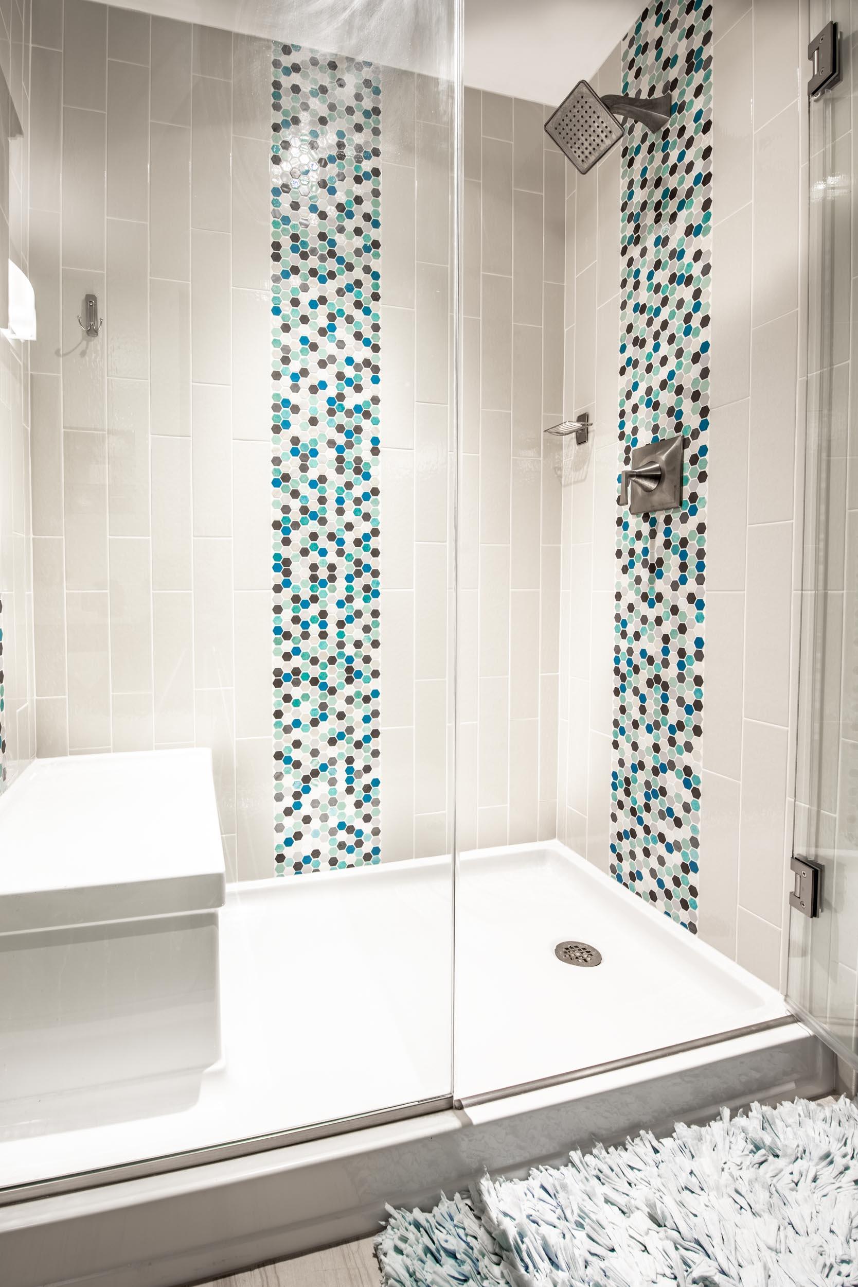 - This multi-colored mosaic provides a pop of color in this condominium bathroom.