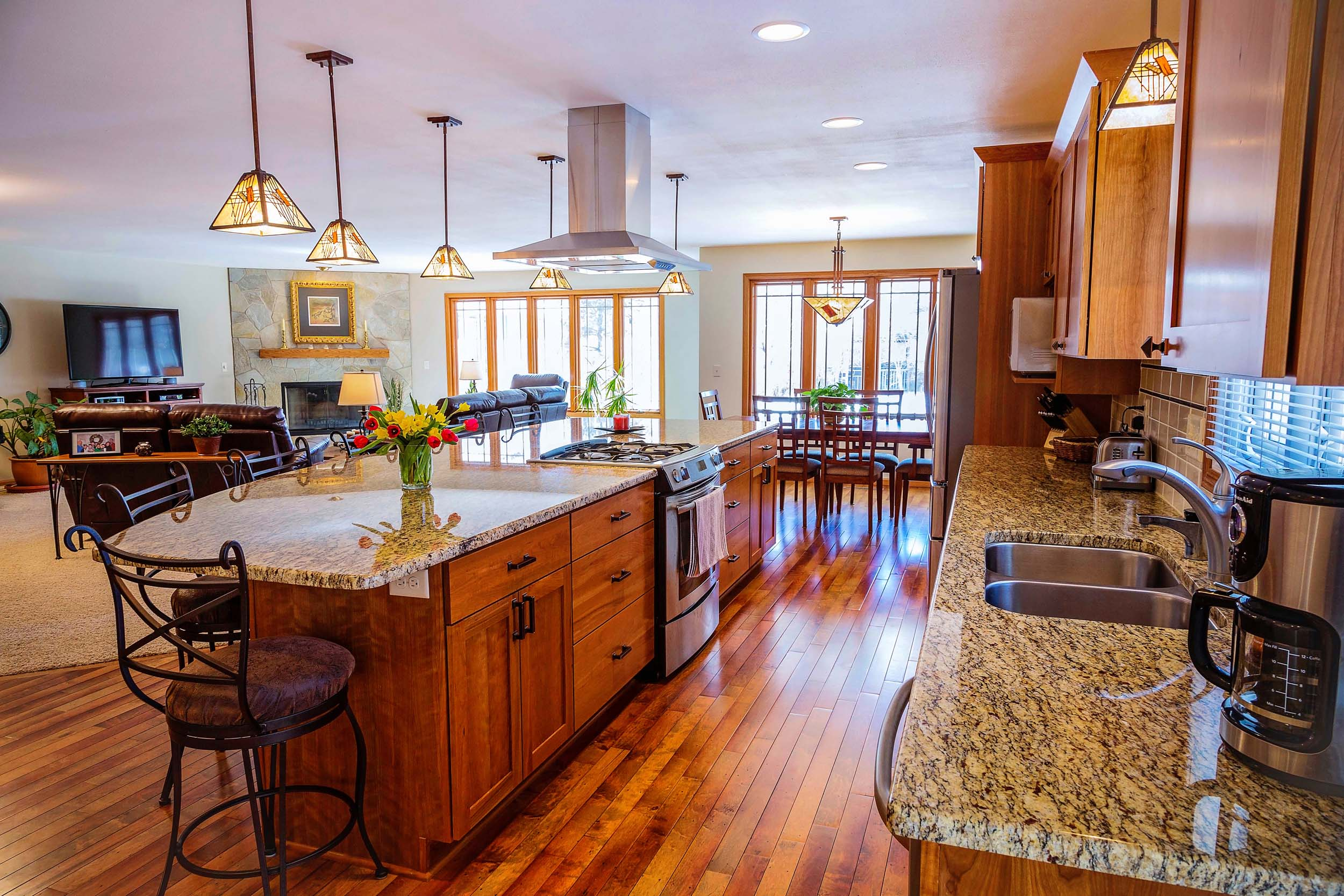 A Grand Floor Plan for Entertaining and Parties - The spaces visible in this photo were formerly divided into 4 different rooms. Converted to a Great Room open floor plan, the island now seats all the grandchildren, and handles the parties that the clients like to host.
