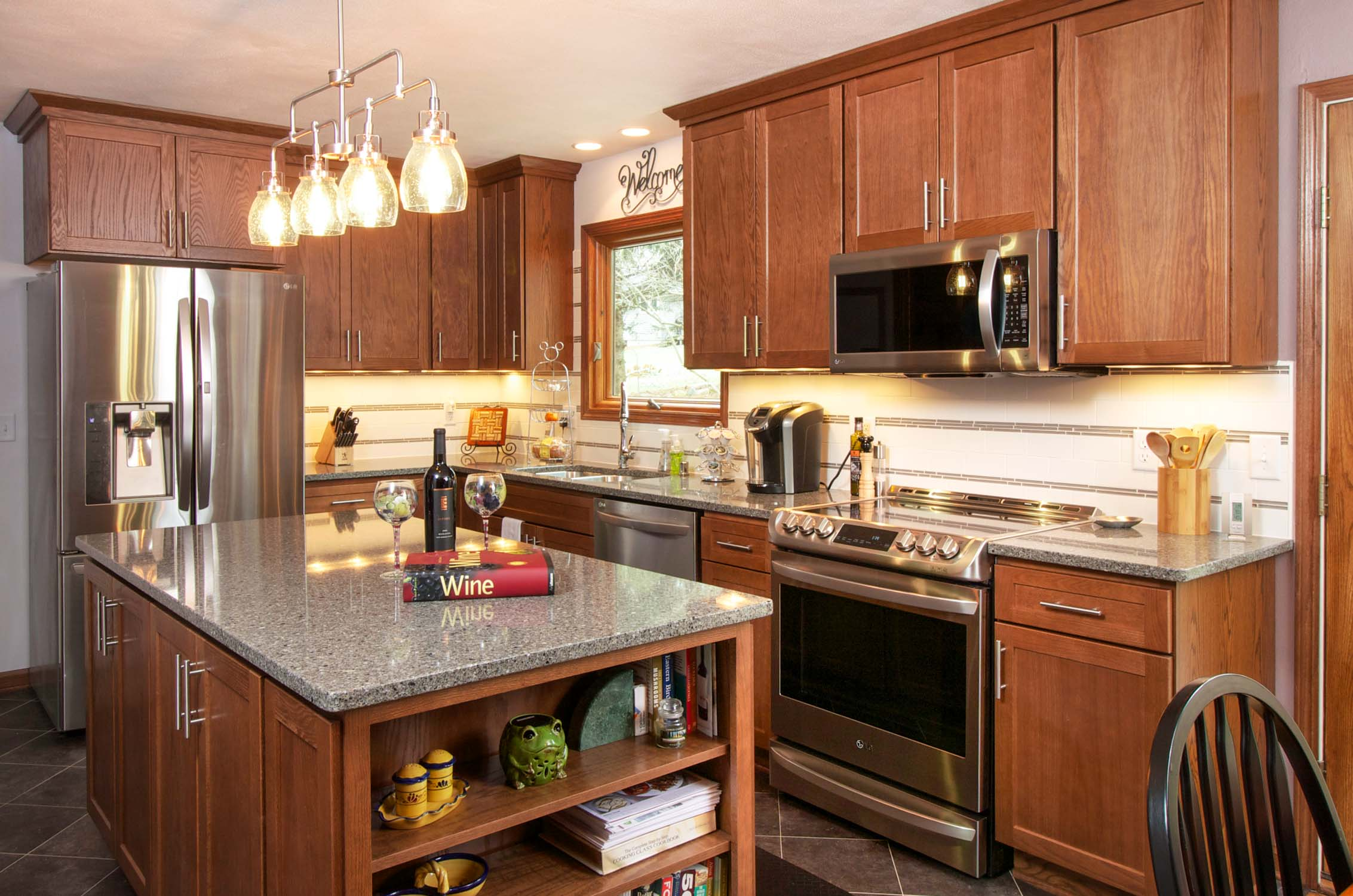 Task Lighting in Small Kitchens - In a smaller kitchen space, task lighting plays a prominent role. With only the island fixture for ambient light, the recessed cans over the sink and undercabinet lights provide the rest of the lighting needed for this kitchen.