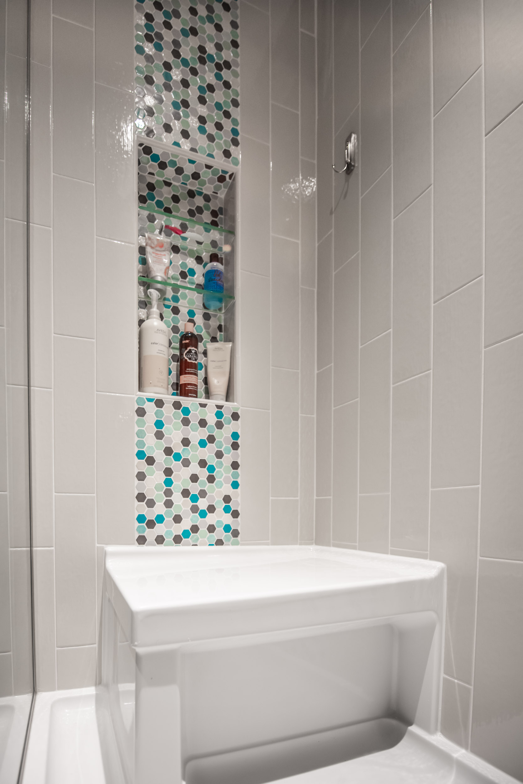 - This niche is precisely integrated with the vertical tile stripe used in 3 parts of this shower at Metropolitan Place condos, Madison.