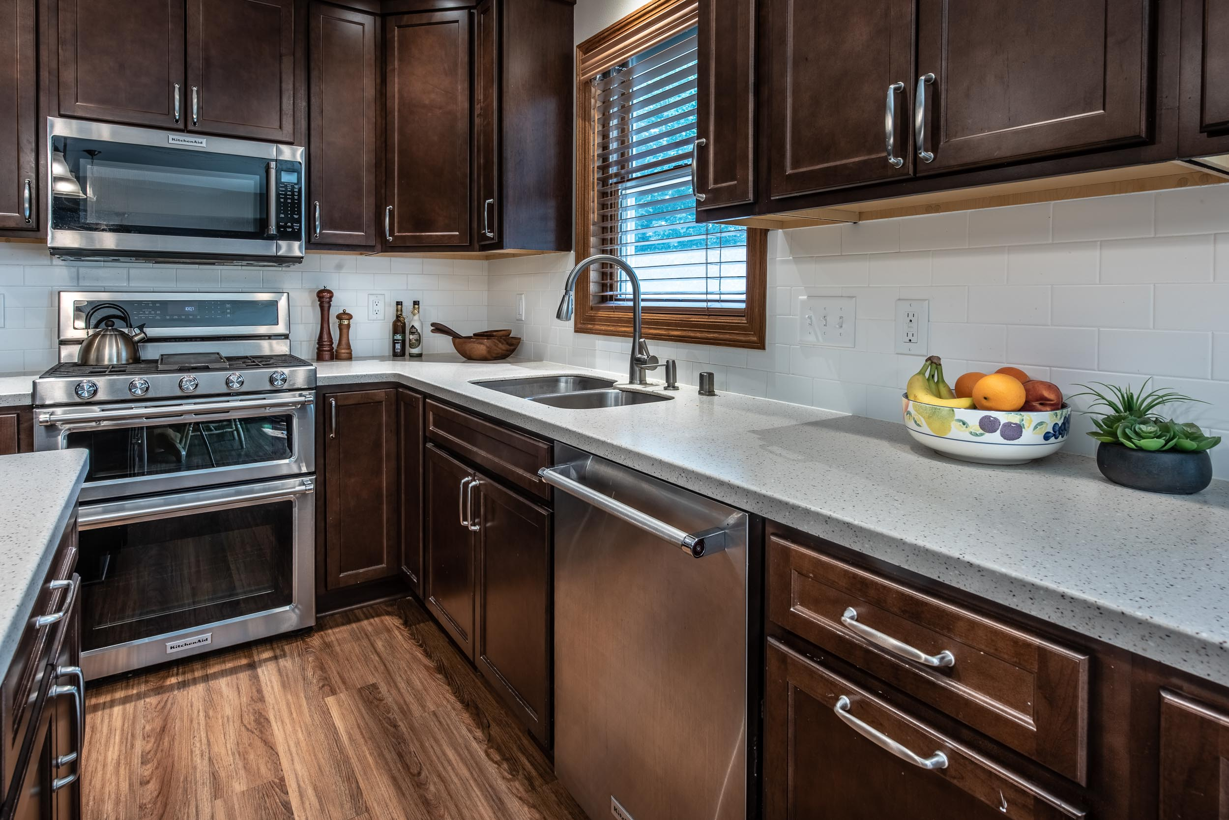 The Countertop is LG Hi-Macs Solid Surface in Macchiato. The Subway Tile Backsplash Is Streamline 3x6 matte tile in Arctic color with Bright White grout.