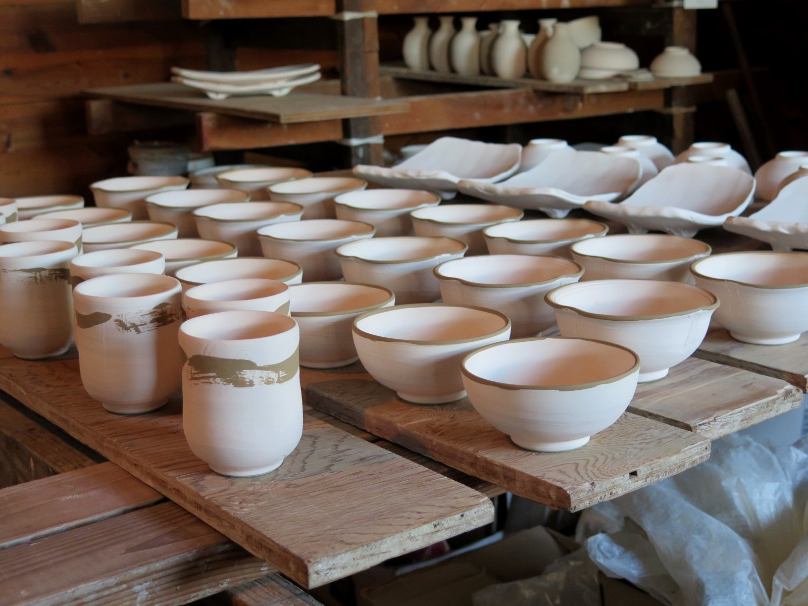 A group of bisqued teacups, bowls and plates.