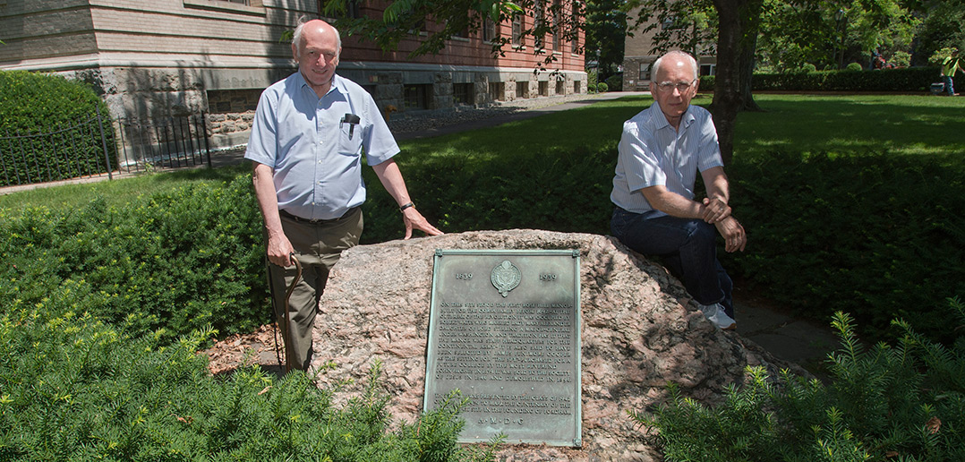 A plaque next to Collins Hall marks the spot where professors Roger Wines and Allan Gilbert (left, right) conducted an archaeological dig into the foundations of Rose Hill Manor, the 18th-century farmhouse that was one of the original buildings at the Rose Hill campus