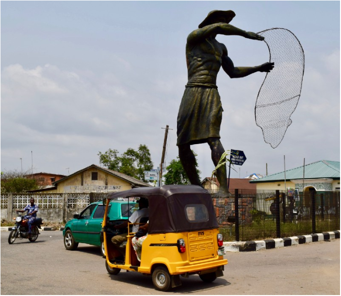The town center of Badgry, Nigeria, where a statue of the small village's main commerce stands today. Keke, the yellow minicabs, and motorbikes are the main source of transportation for most of Nigeria.