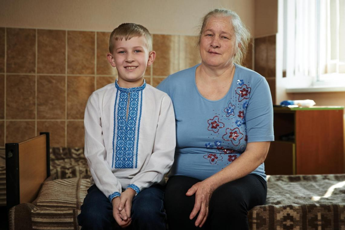 Hanna Prokopyshyn sits with her grandson Dmytro, 9, in the hospital where he receives treatment for bronchial asthma. Dmytro's parents initially were afraid to vaccinate their son due to his condition – a concern doctors dispelled, especially amid Ukraine's measles outbreak. Dmytro has already successfully received the first dose of the MMR vaccine and his parents plan to follow the National Immunization Schedule.