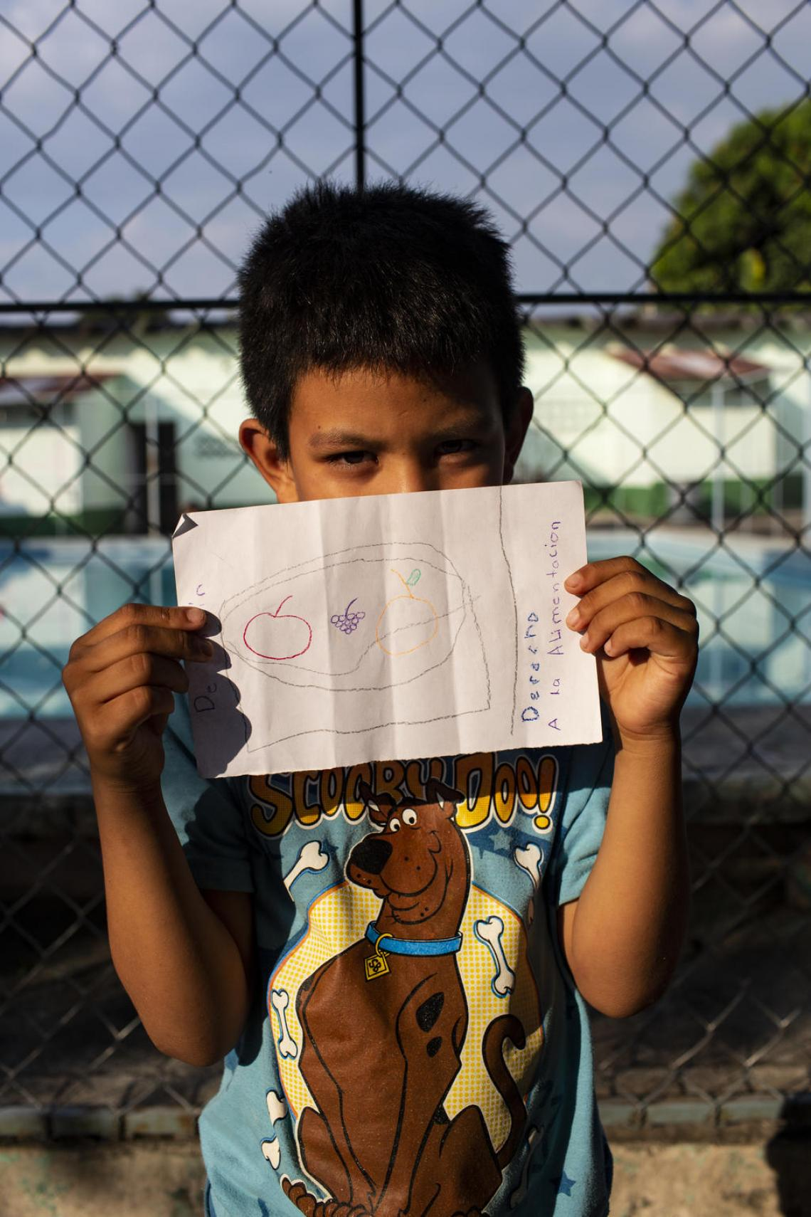 "Jahir, 8, from Honduras, shows off a drawing that depicts his right to eat at the St. Augustine hotel for refugees in Tapachula, Mexico. ""Whether these children stay in Mexico or head further up north, it is crucial that they remain with their families, that they are kept out of detention centers,"" says Paloma Escudero. UNICEF supports the implementation of 'open-door' shelters for migrant and refugee children, where they receive psychosocial support, education, health services and legal assistance."