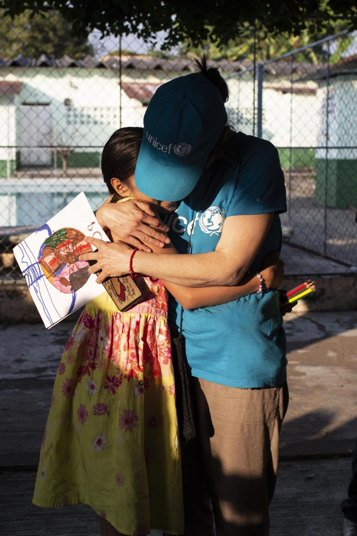 Jennifer's mother was killed by a gang two years ago. A NGO volunteer at the UNICEF-supported St. Augustine hotel for refugees hugs her now after she has travelled with three siblings from San Pedro Sula, Honduras to Tapachula, Mexico. UNICEF advocates with government partners to build on the country's programmes for children on the move, which keep families like Jennifer's together. She has been drawing pictures of her journey.