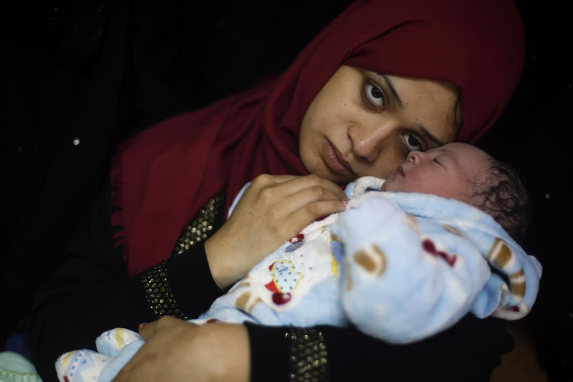 "Gaza City, State of Palestine, 7:30 am:  Samia cuddles her newborn baby boy, Mohammed, 3.8 kg (8.4 lbs.) at Al Shifaa hospital. ""Nothing can describe how happy I am, but I'm worried about my baby's future,"" Samia says. As a result of the political crisis, the degradation in the water, sanitation and hygiene infrastructure and the energy crisis in Gaza persists. UNICEF has continued to provide safe drinking water through solar power water tanks, drinking water taps and hygiene instruction."