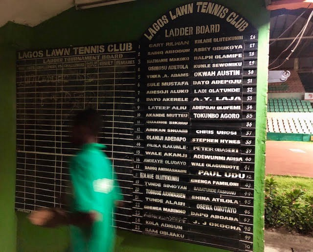 """A """"ball-picker"""" at the Lagos Lawn Tennis Club"""" walks past the ladder standings as he shuffles between matches. Many of the ITF's """"challengers"""" started as ball-pickers."""