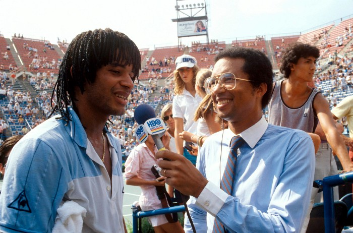 Arthur Ashe interviews Yannick Noah at the U.S. Open in 1983. Ashe discovered Noah at a 1970 exhibition at the Tennis Club de Yaoundé Cameroon, when the then 10-year-old kid started knocking back the black champion's balls. Noah was born in France and brought back to Cameroon at a young age, but Ashe phoned Philippe Chartrier, president of both the Fédération Française de Tennis and the ITF to find him sponsorship.
