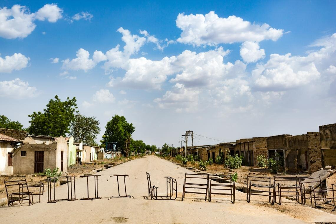 A row of old desks lies across the road on the outskirts of Banki, Nigeria on 1 May 2019. Although the town is still considered one of the most dangerous places in Borno State and is largely deserted, its local primary school has reopened. Refurbished with support from UNICEF, it now has a high perimeter wall, entry and exit gates, and teachers who have been trained to provide psychosocial support.