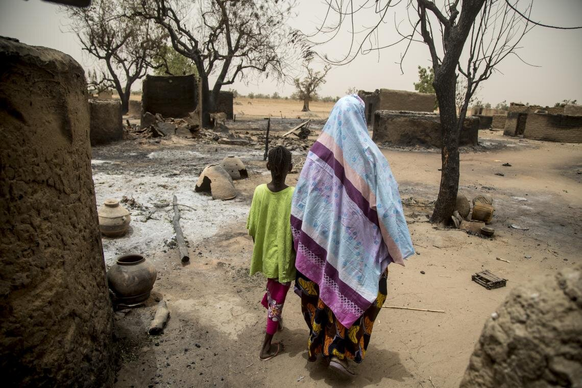 Maïmouna Barry, 45, walks through what is left of the village of Ogossagou-Peulh, Mali, on 2 April 2019 with her daughter Hawa, 10. Less than two weeks before, Maïmouna lost her youngest daughter during an attack on the village, which left more than 150 people dead, one-third of whom were children.   With the help of UNICEF, community learning centres are being set up across the central Sahel region, as safe spaces for children to study, play and receive psychosocial support.