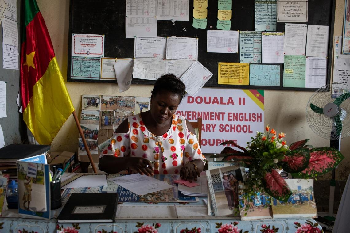 "Delphine Bikajuri, Principal of GEPS Youpwe, a UNICEF-supported government primary school, goes over lesson plans in Douala, Cameroon on 21 May 2019. Two years ago, Ms. Bikajuri had to arrange the release of her own daughter after armed groups kidnapped her from a high school in North-West Cameroon, one of two English-speaking provinces. The soldiers called Ms. Bikajuri and her husband traitors because they teach. ""How would children be leaders of tomorrow, if they are not educated?"" she asks."