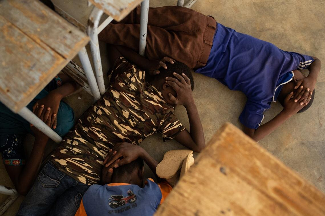 Children take part in an emergency attack simulation and practice sheltering in the event of an assault, at the Yalgho Primary School in Dori, Burkina Faso on 26 June 2019. Threats to teachers, ambushes on schools and the use of schools for military purposes have forced 4,505 schools in the country to close, disrupting education for more than 626,693 children.