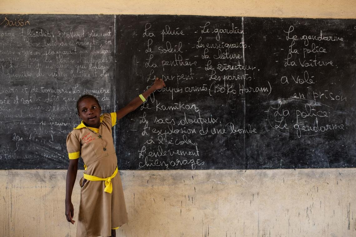 A student goes over blackboard notes on emergency preparedness at a school in Baigaï, a village in Cameroon near the border with Nigeria on 26 May 2019. The programme focusses on teaching children and teachers how to mitigate an armed attack. Despite the risks, people on the front lines of this struggle will not rest until children in their communities are guaranteed the education that is every child's right.