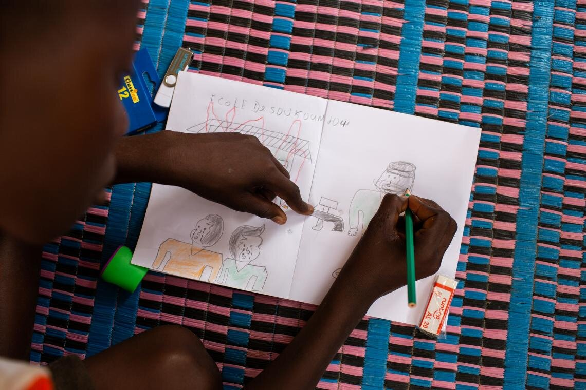 """My father said we have to leave, and so we did, all of us: my parents, grandparents, my sisters and brothers. We all escaped together."" Hussaini has not set foot in a classroom since that day his village was attacked, he explains while drawing pictures during a lesson through the Radio Education in Emergencies programme in Dori, Burkina Faso on 25 June 2019. But his Radio Education facilitator has become a trusted friend. ""Abdoulaye is like my older brother,"" Hussaini says."