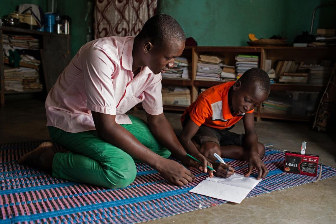 """Abdoulaye (left) guides Hussaini through his lesson on 25 June 2019. Abdoulaye says that people have been deeply affected by the crisis. """"At first, they only threatened schools,"""" he says. """"Nowadays, they actually kill us."""" But he insists that he has not been deterred. """"It's very important for these children to learn,"""" he says. """"They are our younger brothers and sisters. We must help them."""""""