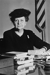 Frances at desk with books and flag.jpg