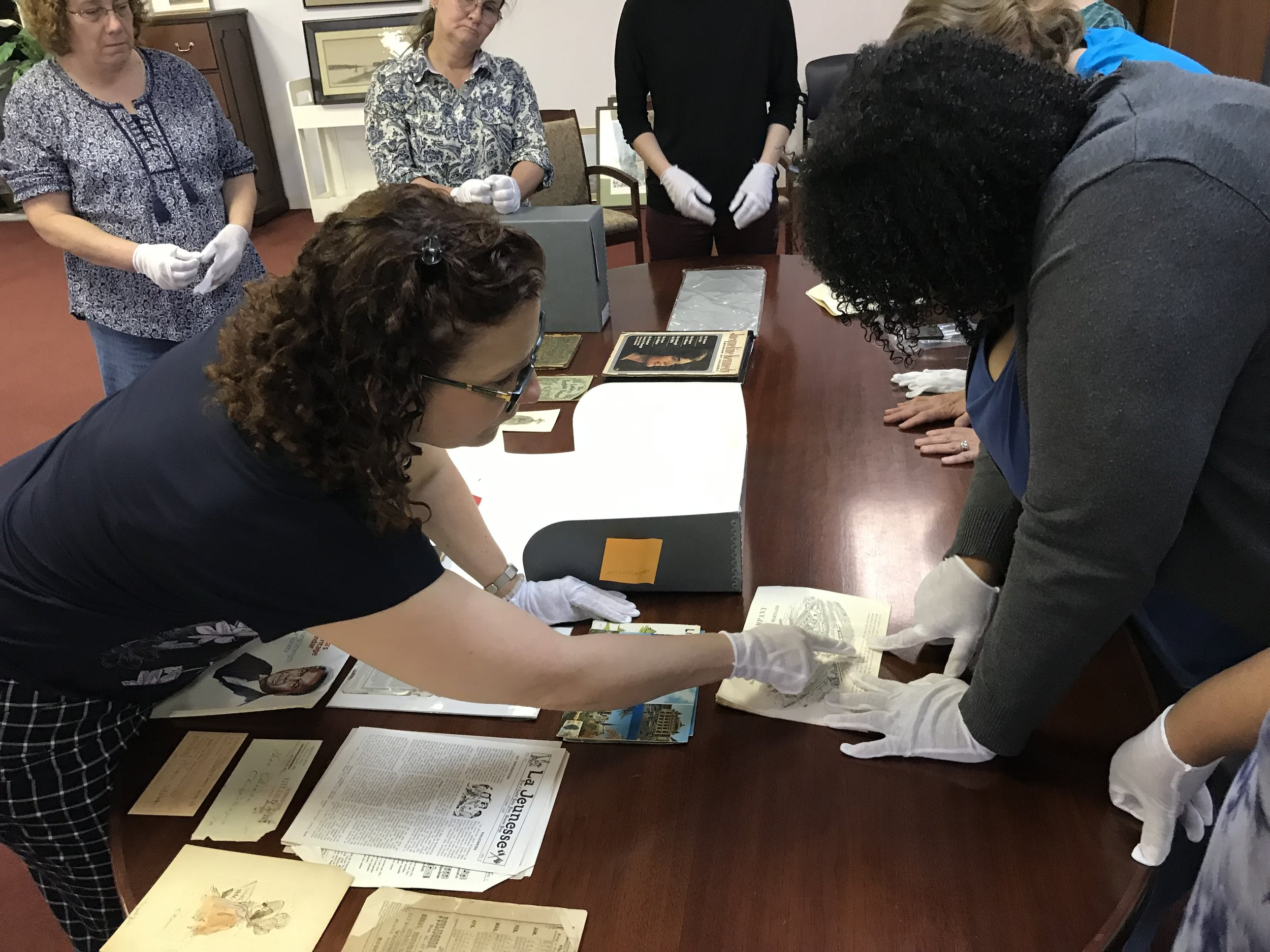Leigh Grinstead, an archival consultant from Lyrasis, trains library staff member, Jazmine Collins, in techniques for handling and storing historic papers.