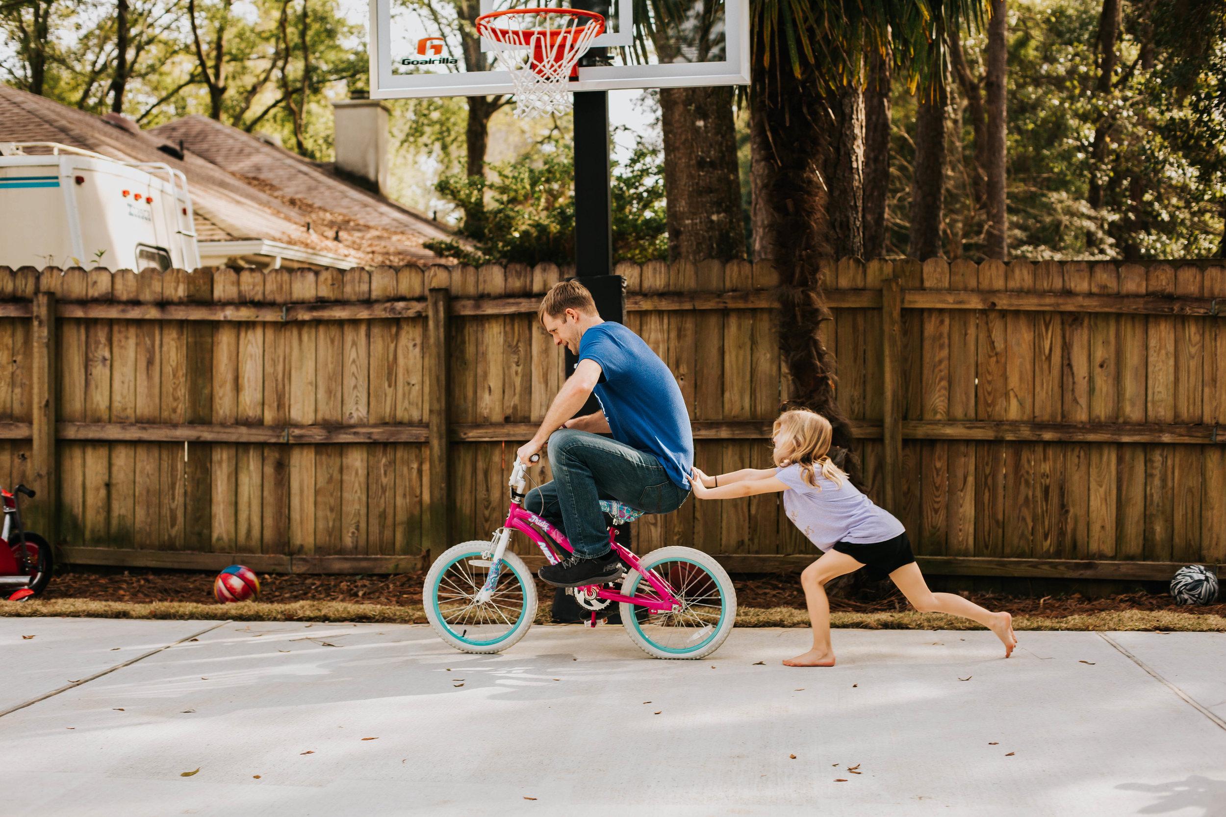 girl pushing daddy on bike in Fairhope Alabama