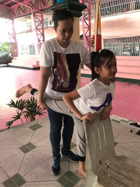 Ballet Manila rehearsal mistress Eileen Lopez checks a student's flexibility during one of the auditions for Project Ballet Futures scholars.